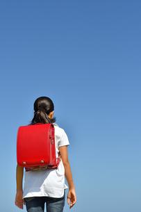 青空に立つ小学生の女の子(後姿)の写真素材 [FYI03398258]