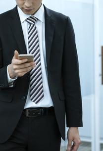 スマートフォンを操作するビジネスマンの手元の写真素材 [FYI03398353]