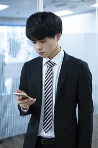 スマートフォンを操作するビジネスマンの写真素材 [FYI03398354]