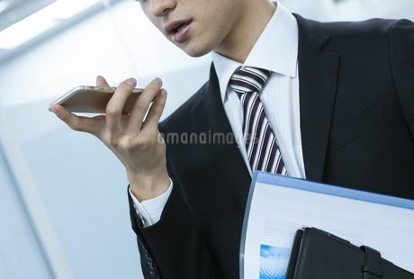 スマートフォンを持つビジネスマンの手元の写真素材 [FYI03398356]