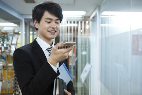 スマートフォンを持つビジネスマンの写真素材 [FYI03398361]
