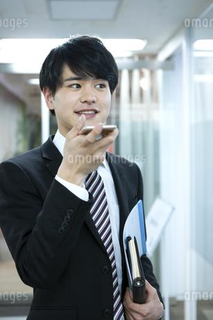 スマートフォンを持つビジネスマンの写真素材 [FYI03398362]