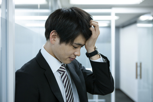 頭を抱えるビジネスマンの写真素材 [FYI03398365]
