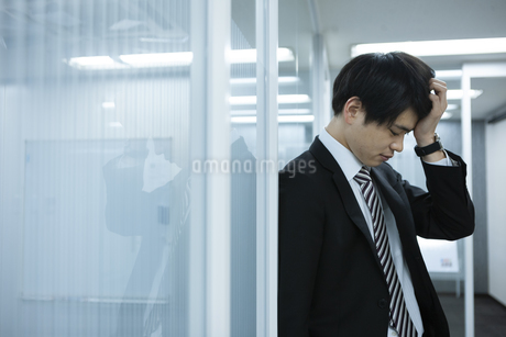 頭を抱えるビジネスマンの写真素材 [FYI03398366]