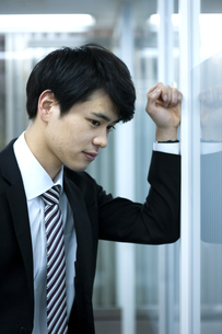 壁に向かって落ち込むビジネスマンの写真素材 [FYI03398367]