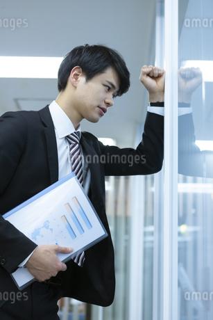 壁に向かって落ち込むビジネスマンの写真素材 [FYI03398368]