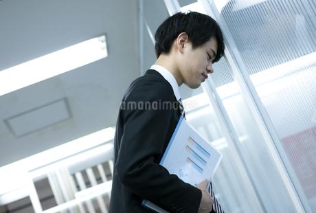壁に向かって落ち込むビジネスマンの写真素材 [FYI03398371]