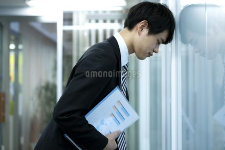 壁に向かって落ち込むビジネスマンの写真素材 [FYI03398372]
