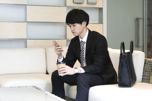 スマートフォンを操作するビジネスマンの写真素材 [FYI03398396]