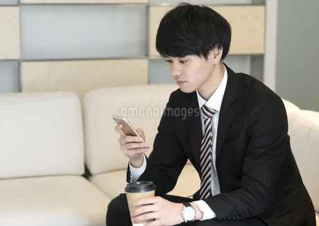 スマートフォンを操作するビジネスマンの写真素材 [FYI03398397]