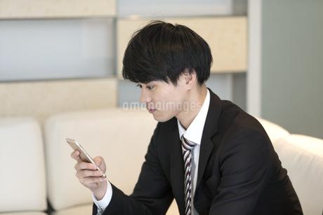 スマートフォンを操作するビジネスマンの写真素材 [FYI03398398]
