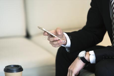 スマートフォンを操作するビジネスマンの手元の写真素材 [FYI03398400]