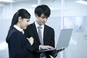 パソコンを見るビジネスマンとビジネスウーマンの写真素材 [FYI03398646]