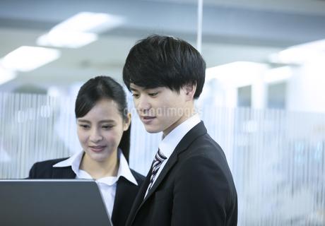 パソコンを見るビジネスマンとビジネスウーマンの写真素材 [FYI03398647]