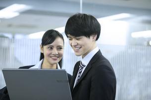 パソコンを見るビジネスマンとビジネスウーマンの写真素材 [FYI03398648]