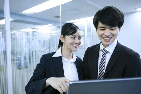 パソコンを見るビジネスマンとビジネスウーマンの写真素材 [FYI03398649]