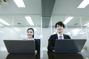 打ち合わせをするビジネスマンとビジネスウーマンの写真素材 [FYI03398668]