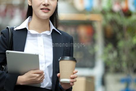 タブレットPCとドリンクを持つビジネスウーマンの写真素材 [FYI03398690]