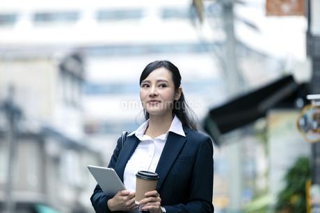 タブレットPCとドリンクを持つビジネスウーマンの写真素材 [FYI03398697]