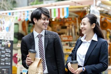 ドリンクを持つビジネスマンとビジネスウーマンの写真素材 [FYI03398702]