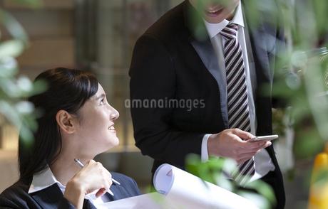 打ち合わせをするビジネスマンとビジネスウーマンの写真素材 [FYI03398719]