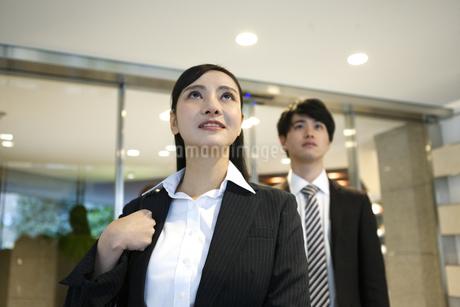 見上げるビジネスウーマンとビジネスマンの写真素材 [FYI03398724]