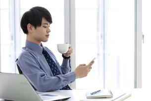 スマートフォンを見るビジネスマンの写真素材 [FYI03398759]