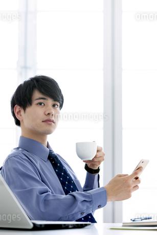 スマートフォンを持つビジネスマンの写真素材 [FYI03398760]