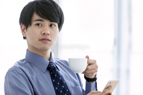 ホットドリンクを持つビジネスマンの写真素材 [FYI03398762]