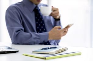 スマートフォンを見るビジネスマンの写真素材 [FYI03398763]