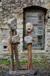 エストニア・タリンの旧市街にあるタリンで最も古い建築と言われるドミニコ修道院の窓枠にある説明プレートと賛美歌を歌う様子の男女の像。旧市街は世界遺産の写真素材 [FYI03399441]