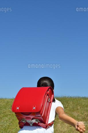 青空で走る小学生の女の子(後姿)の写真素材 [FYI03399475]
