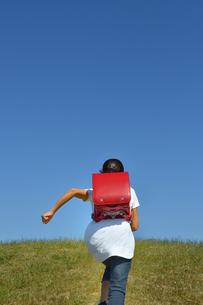青空で走る小学生の女の子(後姿)の写真素材 [FYI03399478]