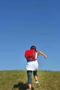 青空で走る小学生の女の子(後姿)の写真素材 [FYI03399480]