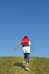 青空で走る小学生の女の子(後姿)の写真素材 [FYI03399482]