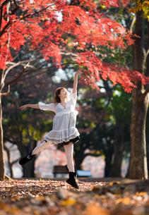 紅葉をジャンプする女性の写真素材 [FYI03399616]