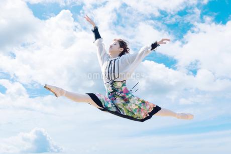 空をジャンプする女性の写真素材 [FYI03399649]