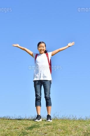 青空でバンザイする小学生の女の子(ランドセル)の写真素材 [FYI03399719]