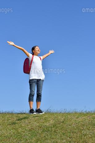 青空でバンザイする小学生の女の子(ランドセル)の写真素材 [FYI03399720]