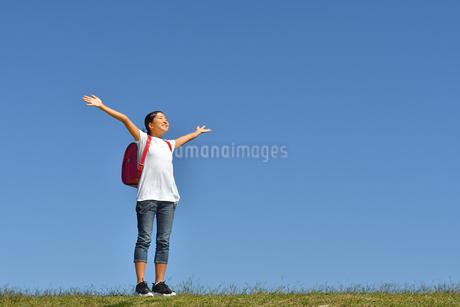 青空でバンザイする小学生の女の子(ランドセル)の写真素材 [FYI03399721]