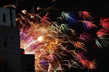 ビルの狭間から見える花火の写真素材 [FYI03399837]