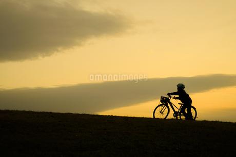 日没の丘で自転車に乗る少年の写真素材 [FYI03399922]