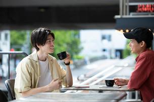 カフェで話す20代男性2人の写真素材 [FYI03400498]