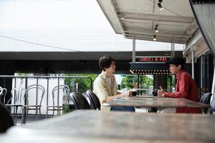 カフェで話す20代男性2人の写真素材 [FYI03400500]