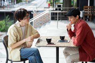 カフェで話す20代男性2人の写真素材 [FYI03400505]
