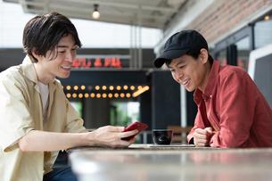 カフェでスマホを示し話す20代男性2人の写真素材 [FYI03400506]