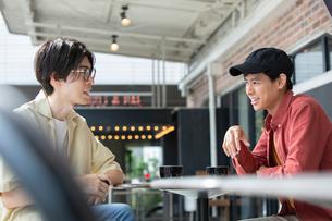 カフェで話す20代男性2人の写真素材 [FYI03400507]