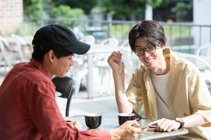 カフェでスマホを示し話す20代男性2人の写真素材 [FYI03400509]