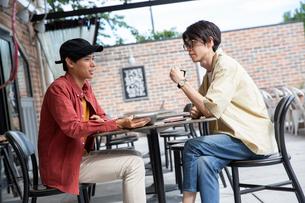 カフェでタブレットを示し話す20代男性2人の写真素材 [FYI03400514]