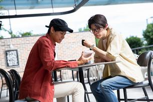 カフェでタブレットを示し話す20代男性2人の写真素材 [FYI03400516]